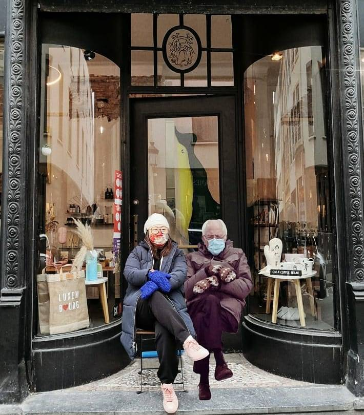 Image of woman in a white beanie, blue mittens and a winter coat sitting in front of a store next to a photoshopped image of Bernie Sanders from the 2021 presidential inauguration
